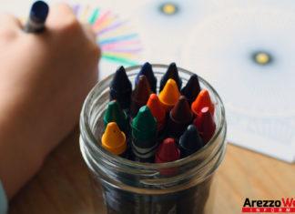 bambino che colora con i pastelli in asilo